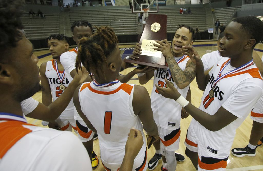 Lancaster forward Darius Davis (23) holds the championship trophy as he celebrates with teammates at mid court following the Tigers victory over Dallas Lincoln, 74-58. The two teams played in the championship game of the Dallas ISD Holiday Invitational boys basketball tournament held at Ellis Davis Field House in Dallas on December 28, 2019.