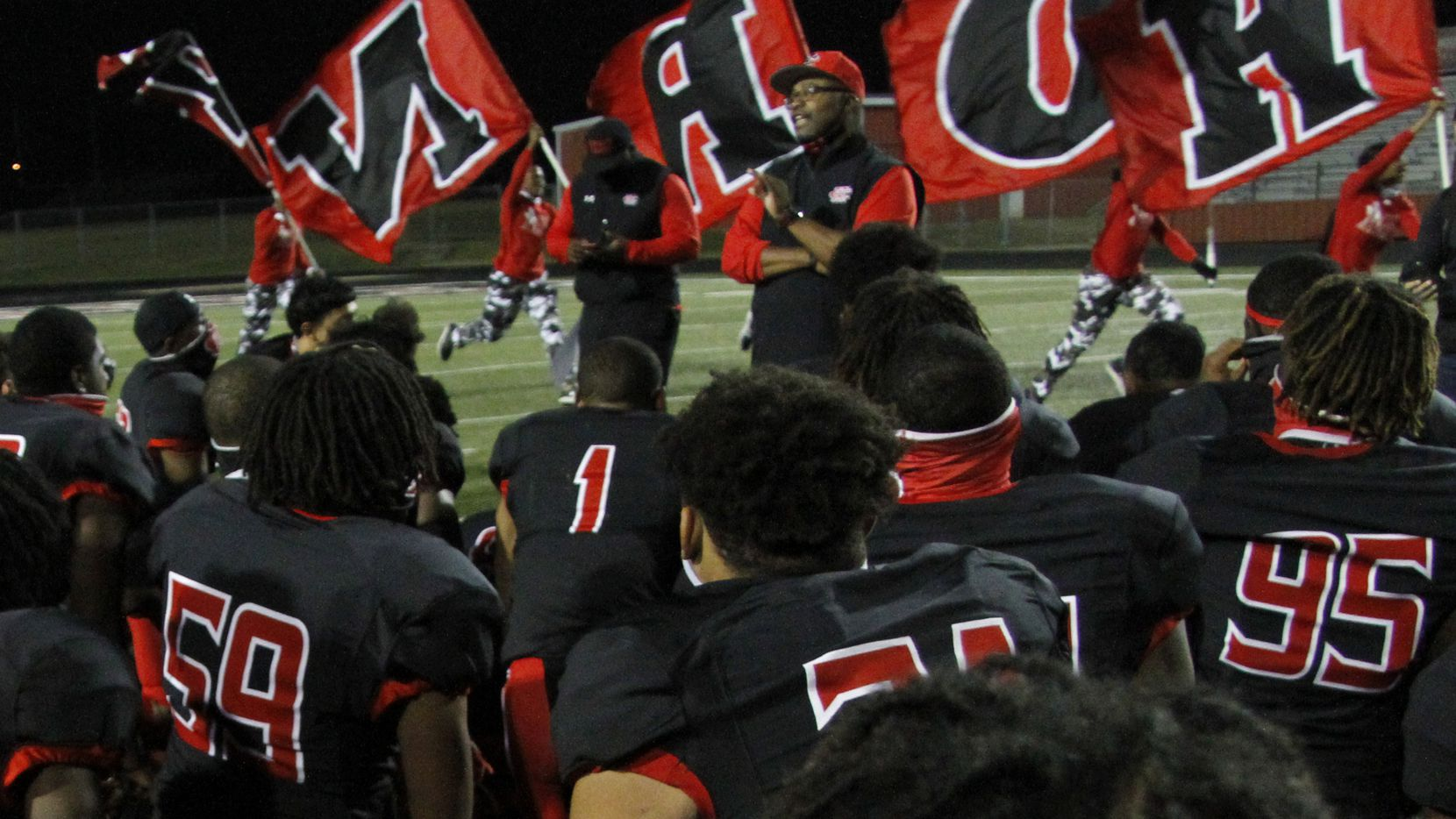 Cedar Hill head coach Carlos Lynn shares a congratulatory message to his team as members of the Red Army Flag Runners sprint past in the background following the Longhorn's 49-42 victory over DeSoto. The two teams played their District 11-6A  football game at Longhorn Stadium in Cedar Hill on November 6, 2020. (Steve Hamm/ Special Contributor)