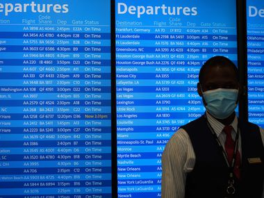 An American Airlines employee wears a face mask while standing in front of flight status displays in Admirals Club lounge at Dallas Fort Worth International Airport Terminal A on Tuesday. (Smiley N. Pool/The Dallas Morning News)