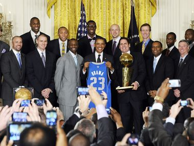 US President Barack Obama (C) holds a jersey as he poses with the NBA Champion Dallas Mavericks in the East Room of the White House on January 9, 2012 to honor the team for their 2011 NBA Championship victory.
