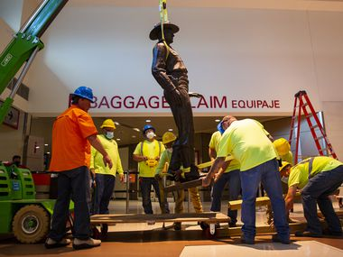 A Phoenix 1 Restoration & Construction crew removes 'One Riot, One Ranger' by Waldine Tauch from the main lobby inside Love Field airport on Thursday, June 4.