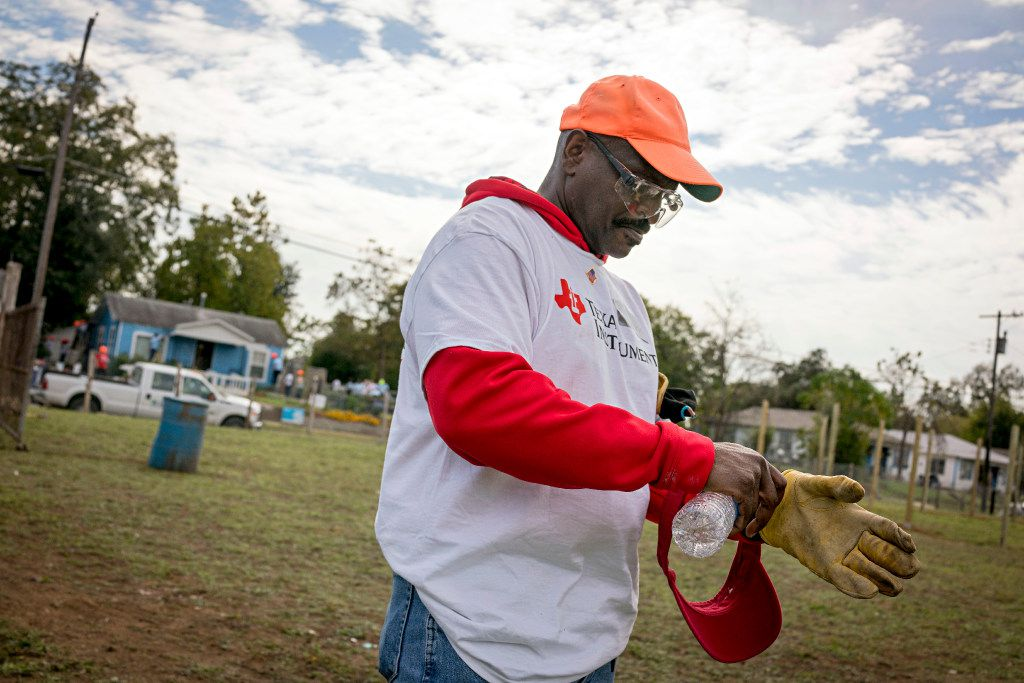 Tyrone Phillips, a U.S. Air Force veteran and project manager at Texas Instruments, puts gloves back on as he prepares to get back to volunteering at the Mill City neighborhood in South Dallas. (G.J. McCarthy/The Dallas Morning News)