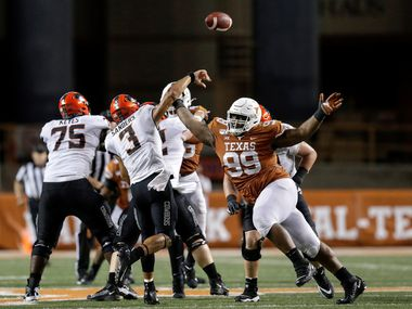 FILE - Oklahoma State quarterback Spencer Sanders (3) throws a pass under pressure by Texas defensive lineman Keondre Coburn (99) in the fourth quarter at Darrell K Royal-Texas Memorial Stadium on Sept. 21, 2019, in Austin. (Photo by Tim Warner/Getty Images)