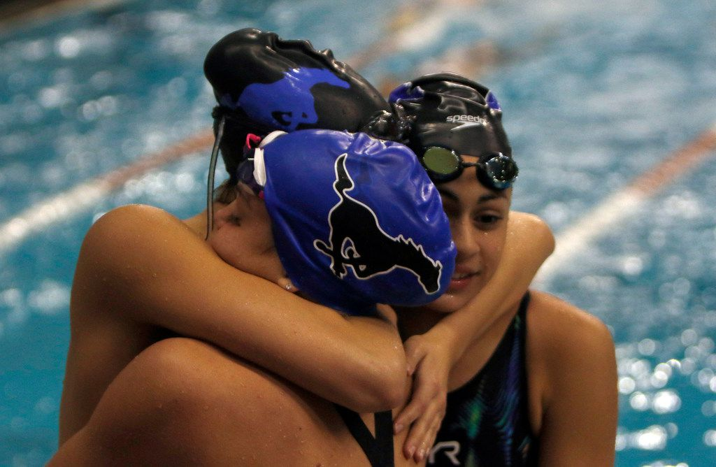 A trio of athletes hug following their swimming event. The UIL Class 6A state swimming and diving finals were held at the University of Texas' Lee and Joe Jamail Texas Swimming Center in Austin on February 15, 2020. (Steve Hamm/Special Contributor).