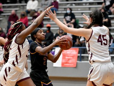 Richardson's Zariah Tillman drives to the basket between Plano's Sanaa Murphy-Showers and Avery Foltz (45) in the second half of a Class 6A girls high school playoff basketball game between Plano vs. Richardson, Monday, Feb. 22, 2020, in Carrollton, Texas. (Matt Strasen/Special Contributor)