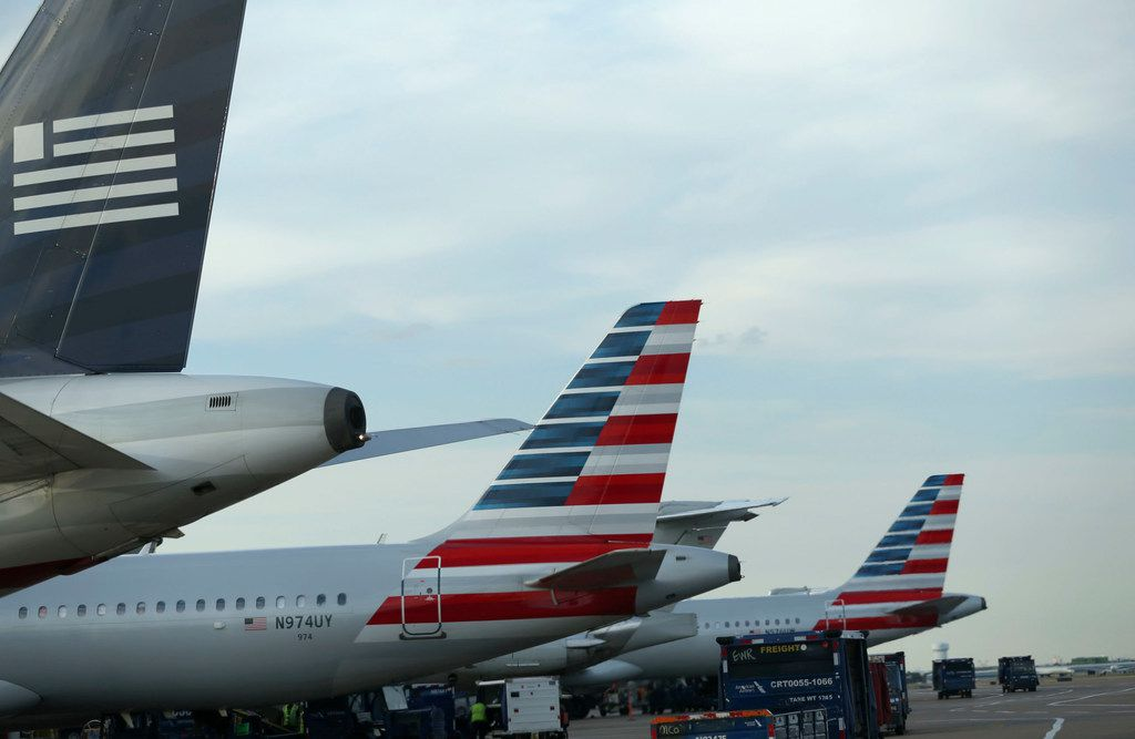 American Airlines jets — and one still painted with the US Airways logo (far left) — wait at the gate as baggage carriers pass by while between flights at Terminal D at DFW International Airport on May 30, 2017.