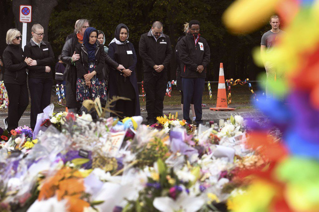 People pay their respects after laying flowers outside the Al Noor mosque in Christchurch on March 21, 2019, six days after the twin mosque shooting massacre that claimed the lives of fifty people. -