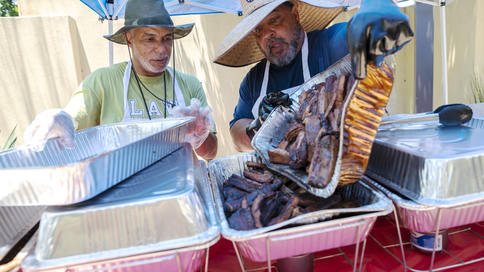 Co-owners Ernest Moore (left) and Ron Evans of Breaux BBQ dished up smoked meats during Saturday's joint Father's Day/Juneteeth event put on by City Men Cook and the African American Museum at Dallas' Fair Park.