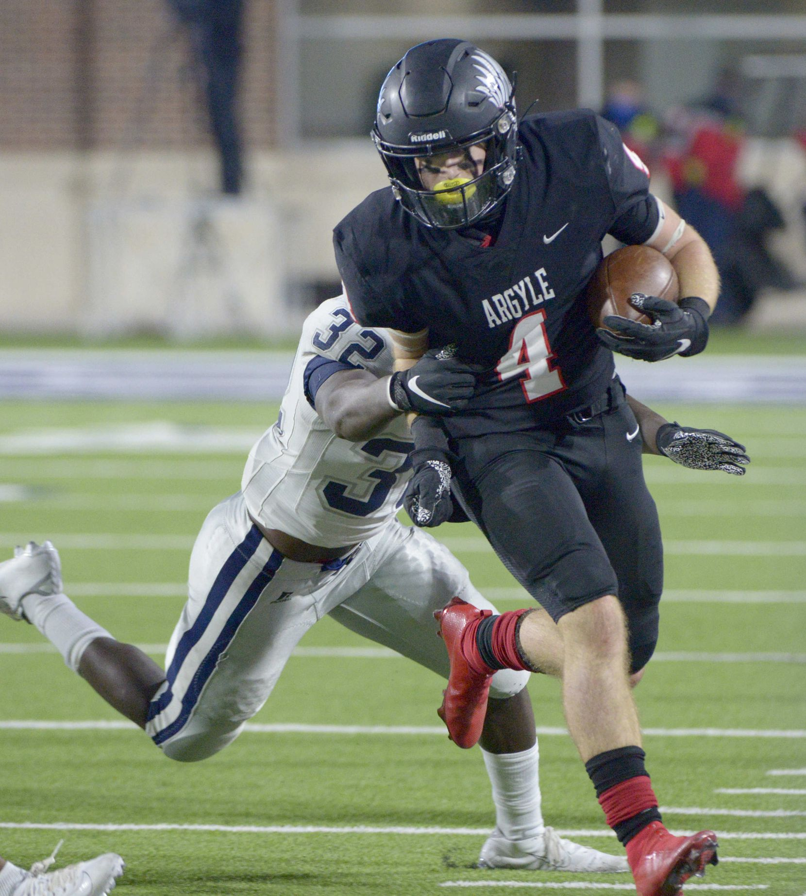 Argyle's Knox Scoggins (4) runs through a tackle attempt by Paris' Keshawn Wallace (32) in the second half during a Class 4A Division I Region II final playoff football game between Paris and Argyle, Saturday, Dec. 5, 2020, in McKinney,  Texas. (Matt Strasen/Special Contributor)