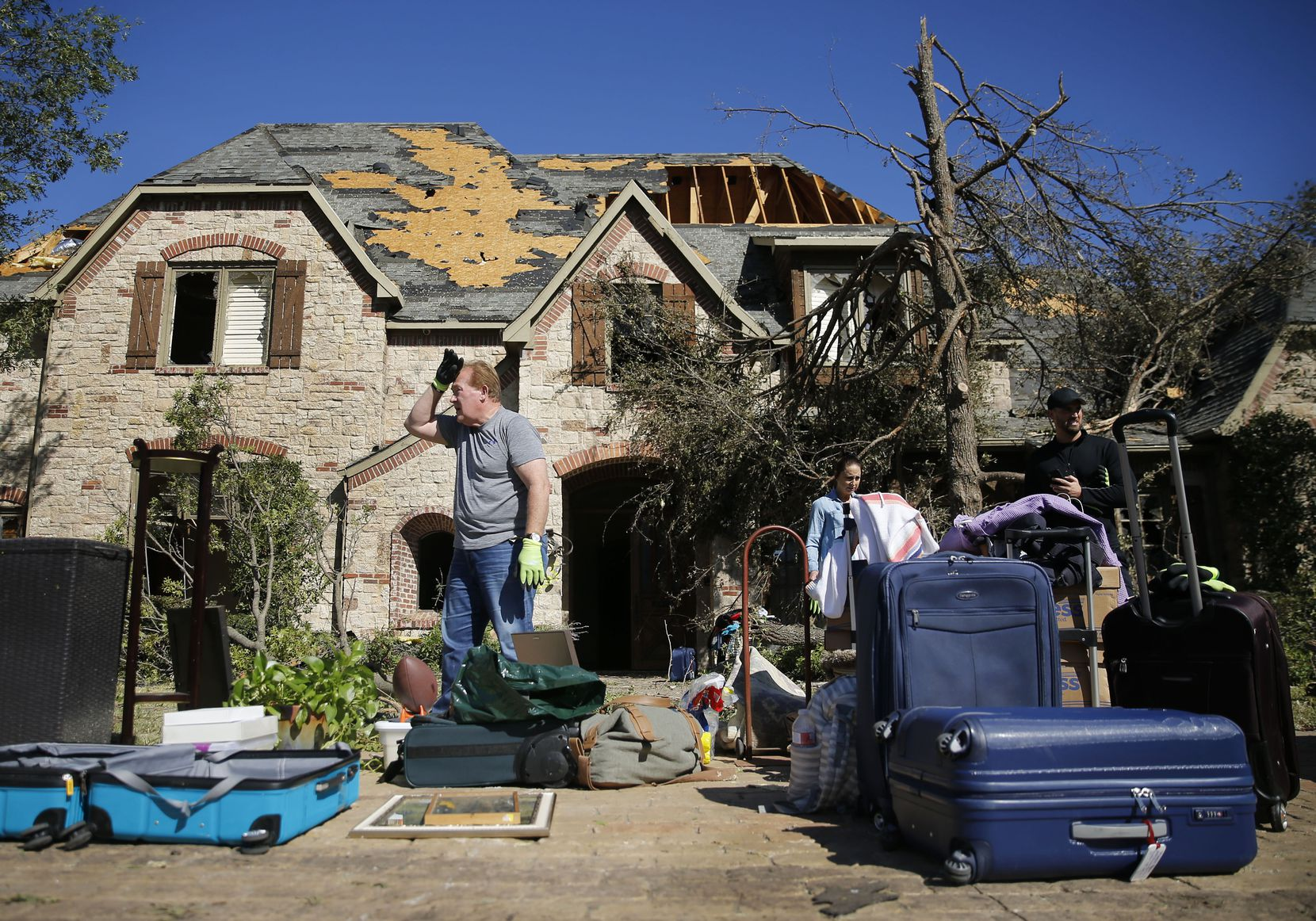 Ken Foster (center) wipes his brow while helping a friend clear some belongings from her damaged home on Pemberton Drive in Dallas, Monday, October 21, 2019. A tornado tore through the neighborhood knocking down trees and ripping roofs from homes.