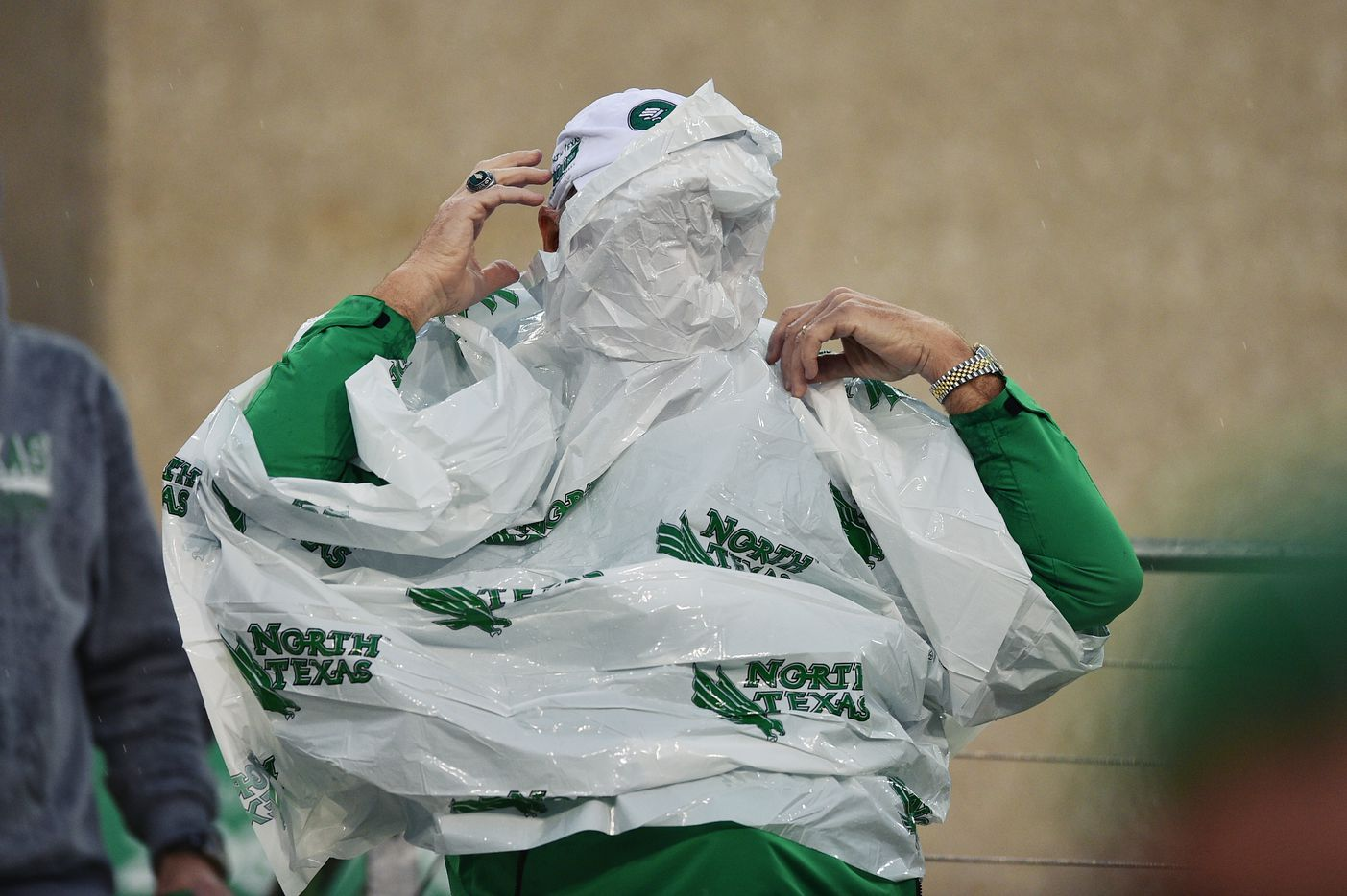 A North Texas Mean Green fan fights against the wind as he tries to put on a poncho during a game against Florida International, in November 2014, at Apogee Stadium in Denton.