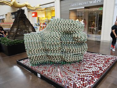 """Marcia Johnson of Ridgemont Commercial Construction takes one last look at the """"Hulk's Hand"""" the team built with Boka Powell during Canstruction at NorthPark Center in September."""