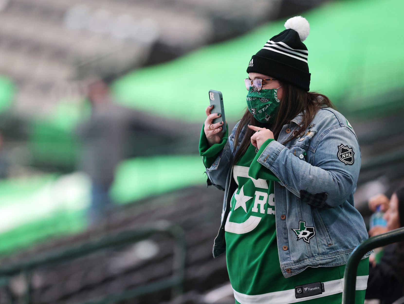 A Dallas Stars fan takes record as the Dallas Stars are introduced in a game against the Nashville Predators at American Airlines Center on Friday, January 22, 2021in Dallas. (Vernon Bryant/The Dallas Morning News)