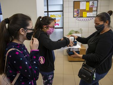 (From left) Adlemi Morales, 13, and Emeline Morales, 11, grab Wi-Fi hotspots provided by DISD from their mom Imelda Tinajero at Young Women's STEAM Academy at Balch Springs on April 24, 2020 in Dallas. Texas won't require masks in a return to school in the fall.