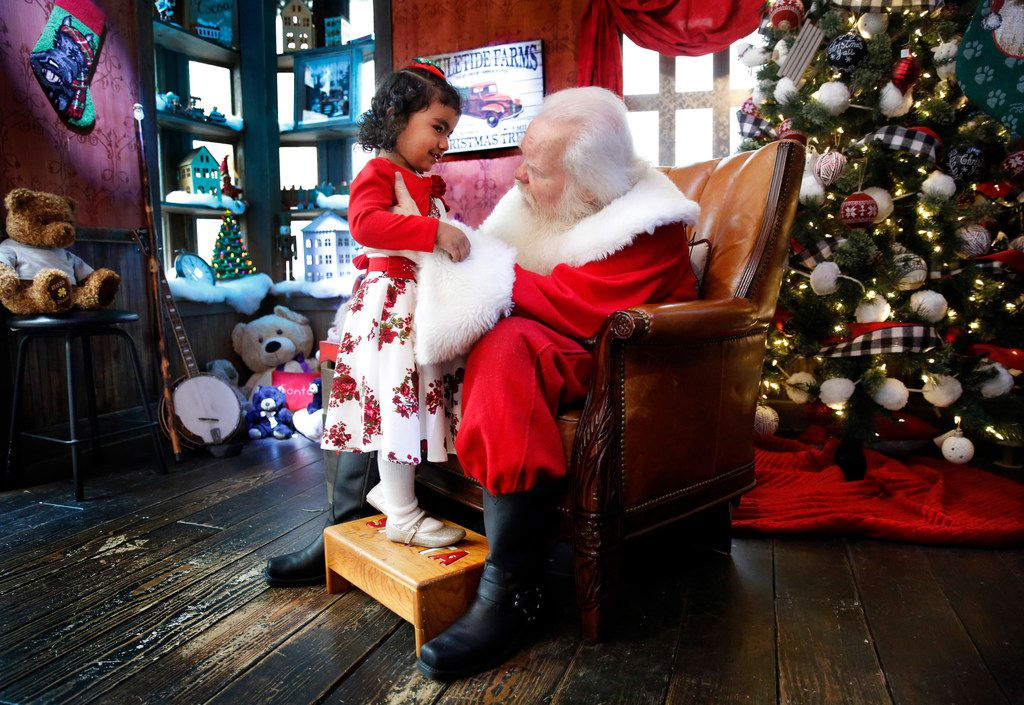 Santa Claus listens to 3 yr-old Abigail Campos of Richardson as she makes a visit to his cottage house at NorthPark Center in Dallas on Dec. 13, 2018. For the past 30 years, Carl Anderson has portrayed Santa at NorthPark. He has story time for children before sitting and listening to their Christmas wishes. (Tom Fox/The Dallas Morning News)