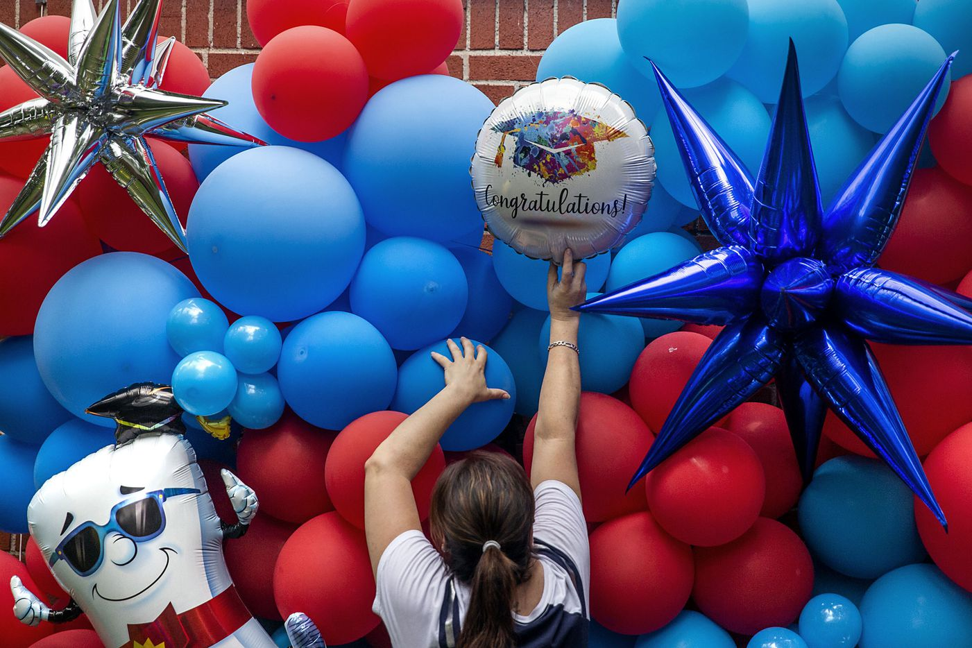 """Mary Ullah helps her daughter — a professional balloon decorator and owner of Laura's Loons —   install a 'Class of 2020' balloon wall for Ullah's son, Israel, at their home in the Pleasant Grove neighborhood in Dallas on Thursday, May 14, 2020. Israel was devastated when he found out that the school's graduation ceremony would be held virtually due to the COVID-19 pandemic, Israel's sister, Laura, said. """"I wanted him to get that spunk back that he lost when he found out,"""" she said. """"Balloons lift the mood immediately, and I just wanted to lift his mood and do something that was just for him."""""""