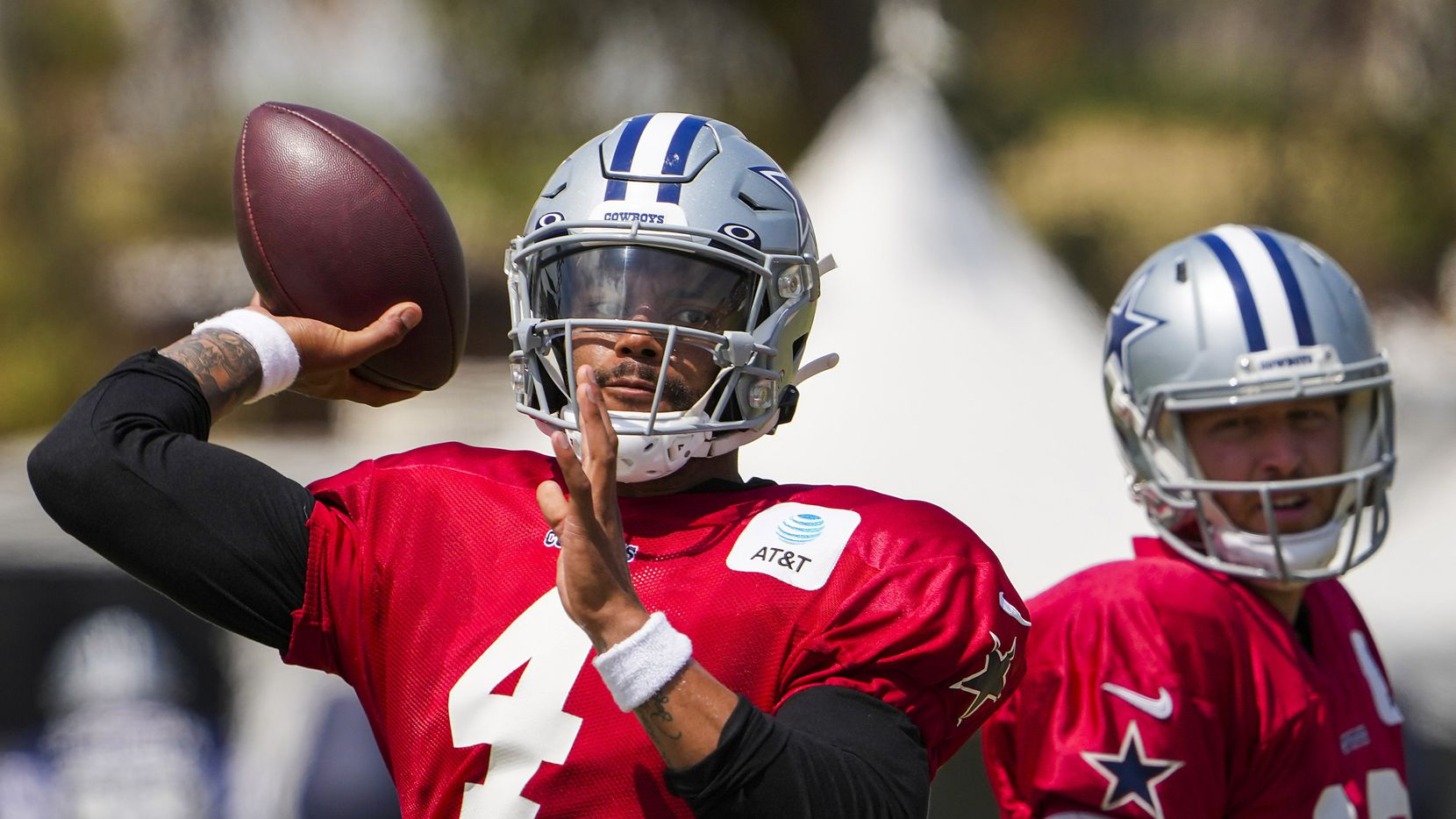 Dallas Cowboys quarterback Dak Prescott (4) throws a pass as quarterback Cooper Rush (10) looks on during a practice at training camp on Wednesday, July 28, 2021, in Oxnard, Calif.
