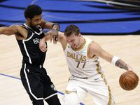 Dallas Mavericks guard Luka Doncic (77) forces his way past Brooklyn Nets guard Kyrie Irving (11) during the second quarter at the American Airlines Center in Dallas, Thursday, May 6, 2021.