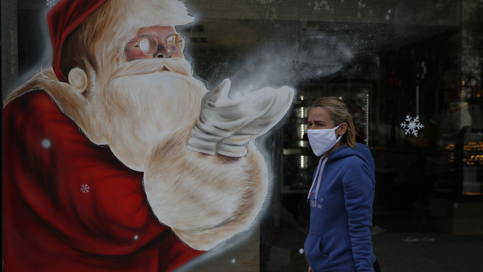 A woman wearing a face mask passes a Santa Claus mural that decorates the store window of a bakery in Athens.