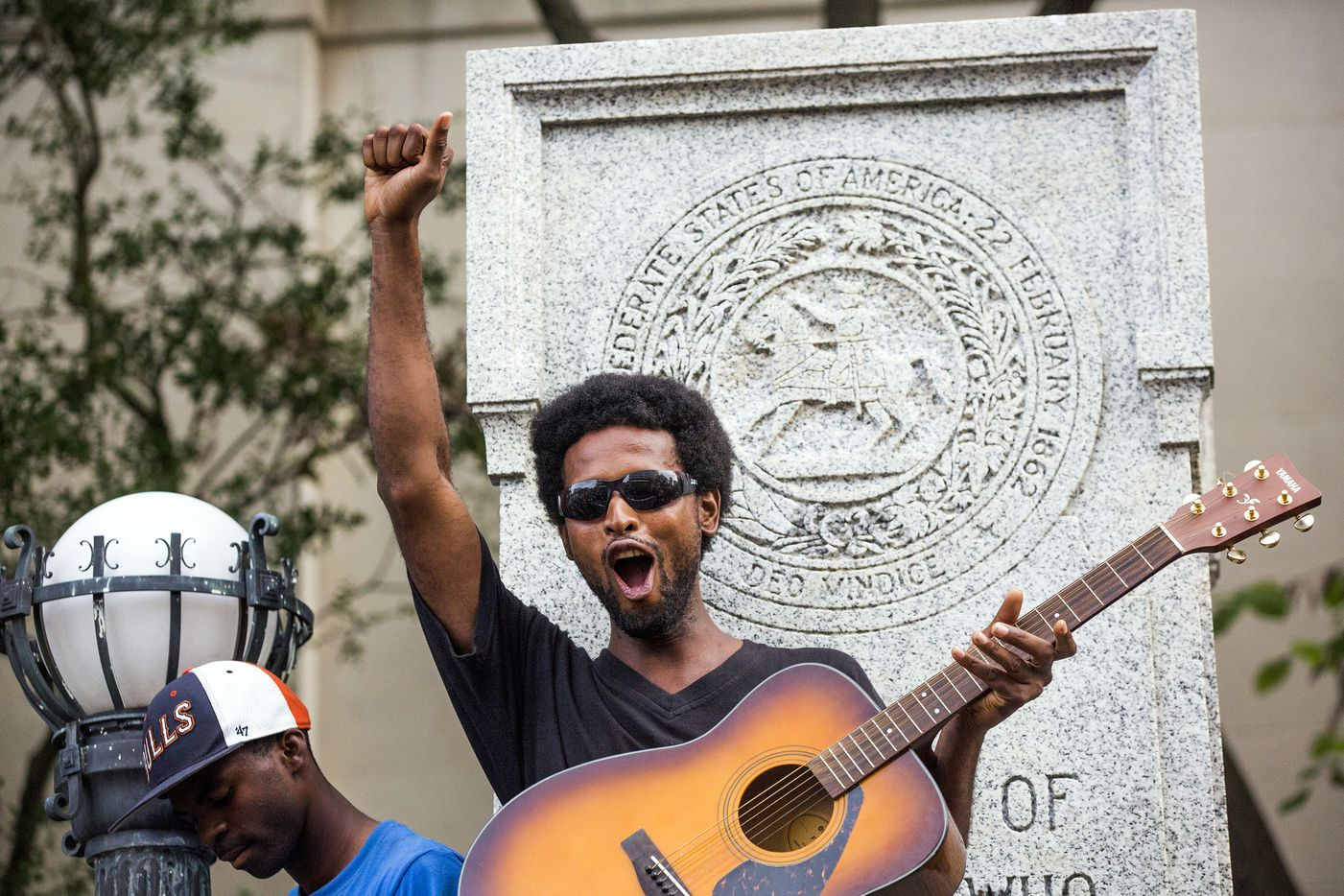 Isaiah Wallace plays his guitar standing on the base that formerly supported a Confederate soldier statue after a group of protesters pulled it down during a rally Monday, Aug. 14, 2017, in Durham, N.C. Protesters toppled the nearly century-old statue of a Confederate soldier Monday at the rally against racism. The Durham protest was in response to a white nationalist rally held in Charlottesville, Va., over the weekend.