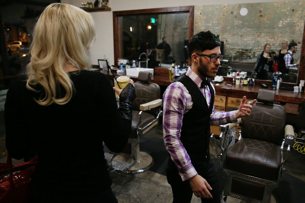 Co-owner Corey Good walks in the barbershop while giving a tour to Elisa Davis (left), who goes by Missy Lisa, and her sister, Ashley Davis (not pictured), inside High & Tight.