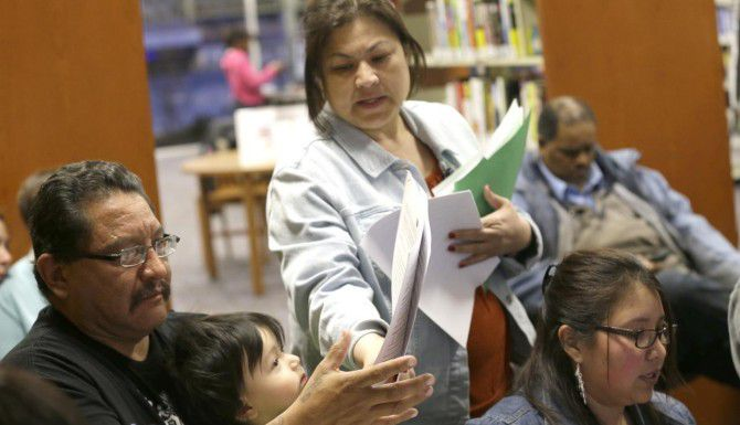 Delaila Hernández ayuda a Fred Cárdenas con sus papeles para inscribirse en la Ley de Cuidado de Salud Asequible en una una biblioteca pública de Fort Worth. El número de latinos sin seguro se ha reducido en un 12%, según un estudio. (AP/LM OTERO)