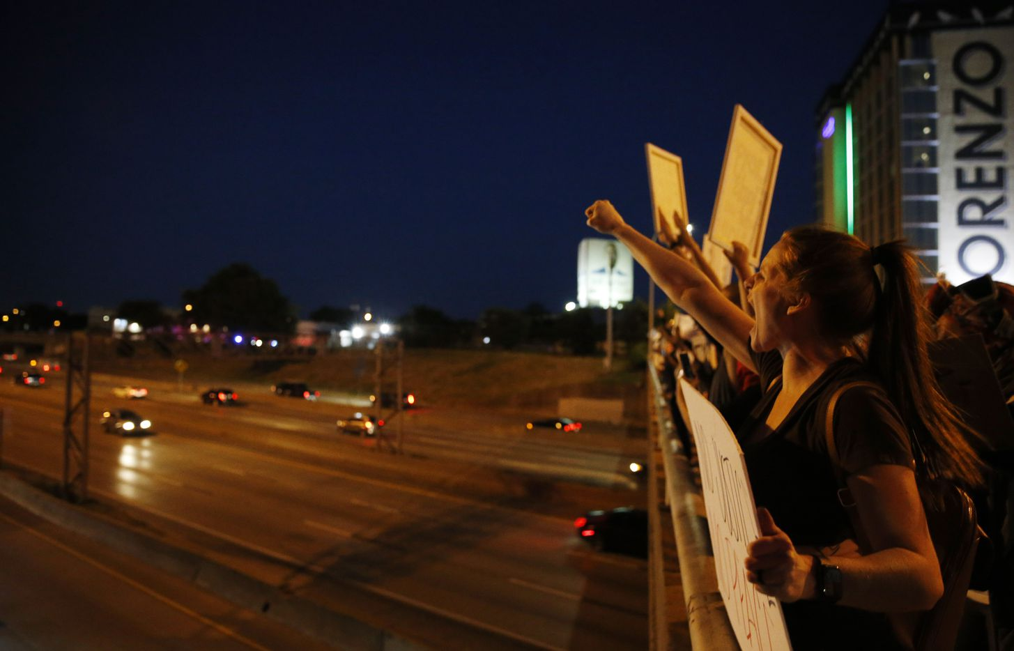 Protesters yell and cheer out on the Akard St. bridge to traffic along Interstate 30 during a demonstration against police brutality in downtown Dallas, on Friday, May 29, 2020. George Floyd died in police custody in Minneapolis on May 25.