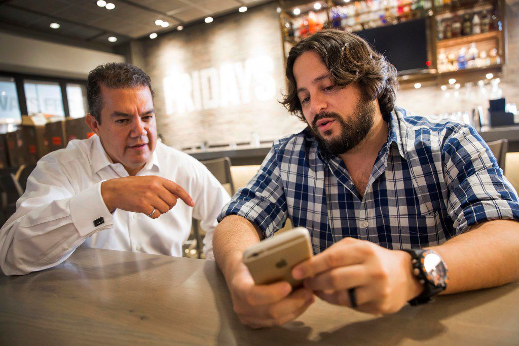 Ben Lamm (right), CEO and co-founder of Conversable, demonstrates the use of a chatbot his company has developed, for Sherif Mityas, vice president of strategy and brand initiatives for TGI Friday's, at the chain's corporate offices Sept. 22 in Dallas.