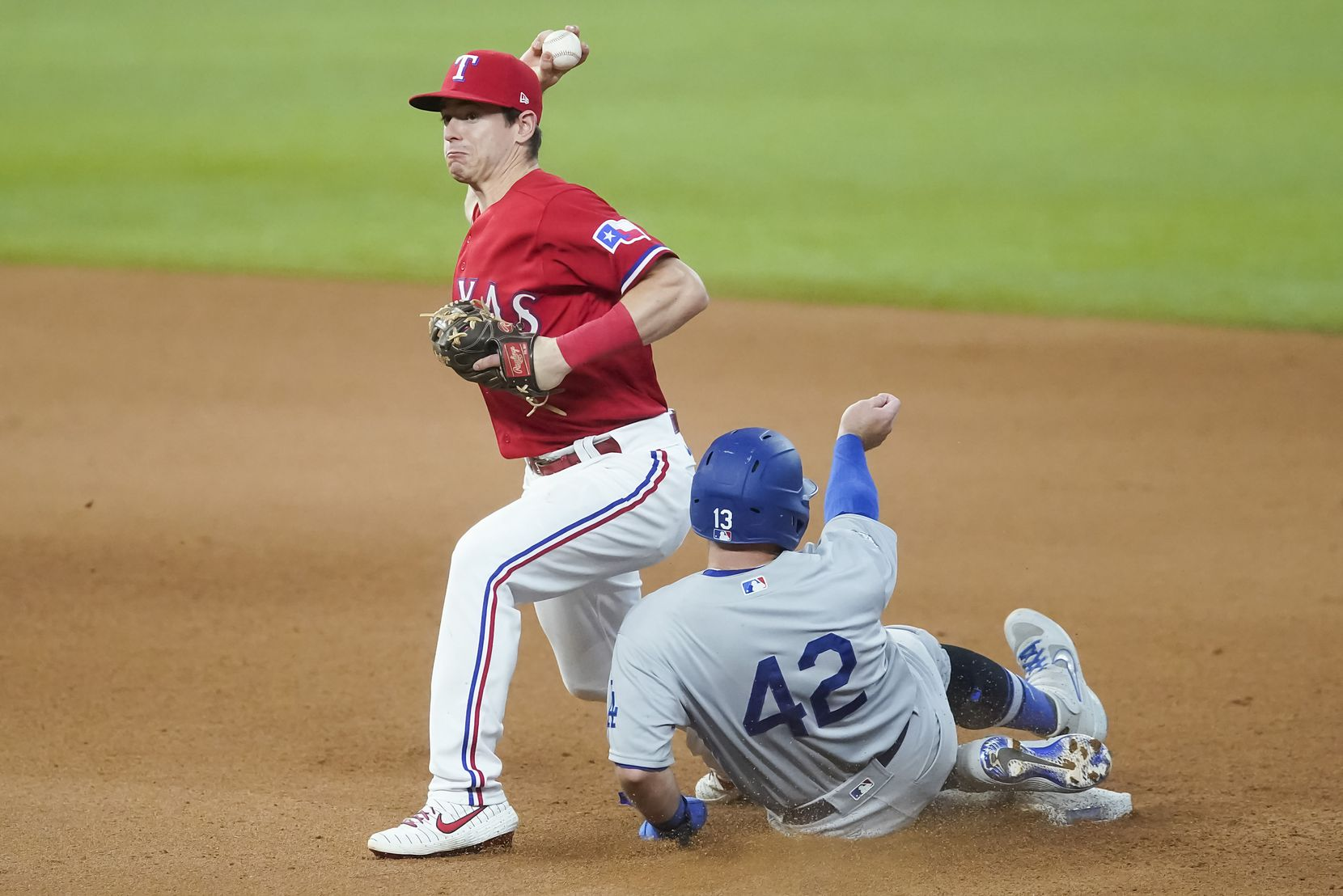 FILE - Rangers second baseman Nick Solak makes a relay over Dodgers third baseman Max Muncy to turn a double play during the seventh inning at Globe Life Field on Sunday, Aug. 30, 2020.