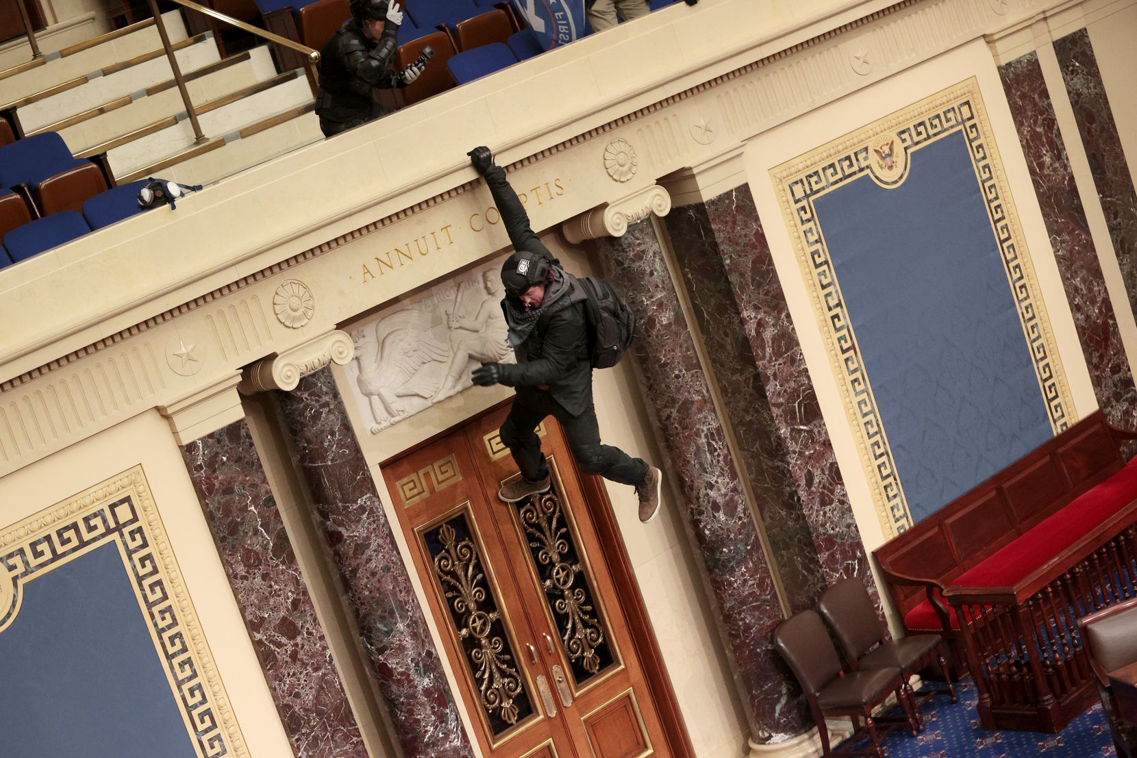 A protester hangs from the balcony in the Senate Chamber on January 6, 2021, as a mob overruns the Capitol, interrupted a joint session of Congress that later ratified President-elect Joe Biden's 306-232 Electoral College win over President Donald Trump.