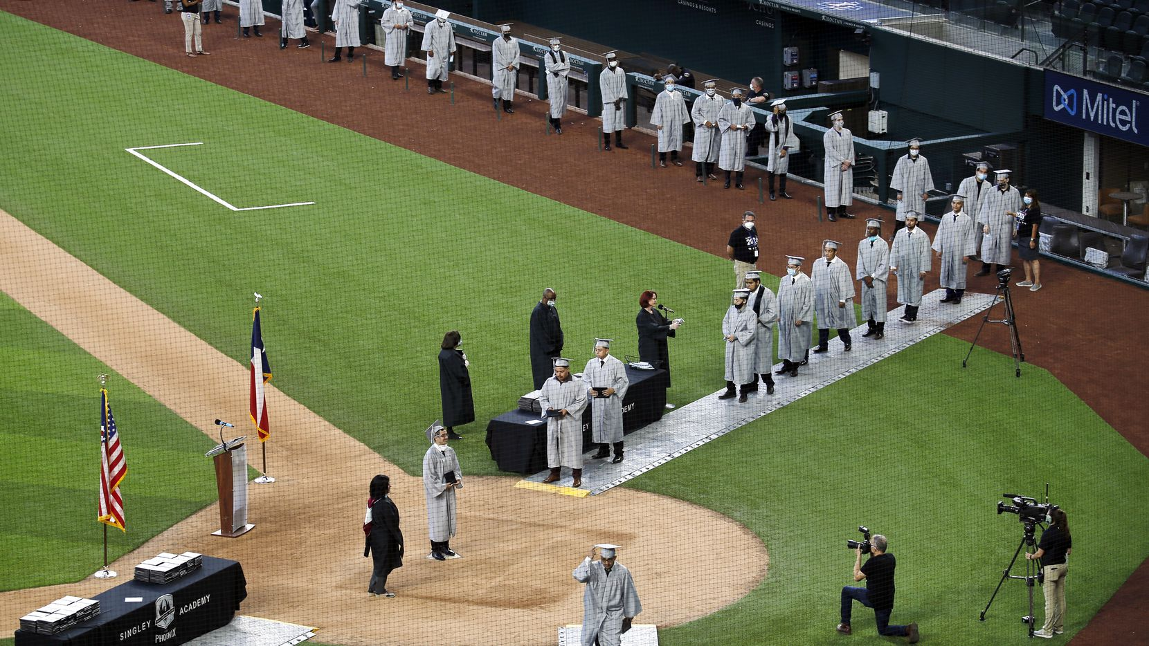 Irving's Jack E. Singley Academy graduates file past the Texas Rangers dugout, onto the field and across home plate where they have a photo made with their diploma at Globe Life Field in Arlington, Texas, Friday, May 29 2020. The graduation ceremony is the first public event held at the newly constructed ballpark. Because of the COVID-19 pandemic, previous events including the start of the Texas Rangers season have been put on hold. Singley Academy is the first of 49 graduations from 18 Independent School Districts in North Texas that will take place at Globe Life Field through the end of June.