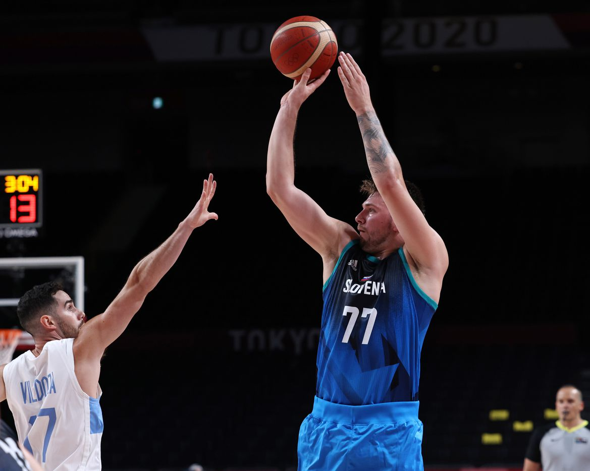 Slovenia's Luka Doncic (77) shoots over Argentina's Luca Vildoza (17) in the first half of play during the postponed 2020 Tokyo Olympics at Saitama Super Arena on Monday, July 26, 2021, in Saitama, Japan. Slovenia defeated Argentina 118-100. (Vernon Bryant/The Dallas Morning News)