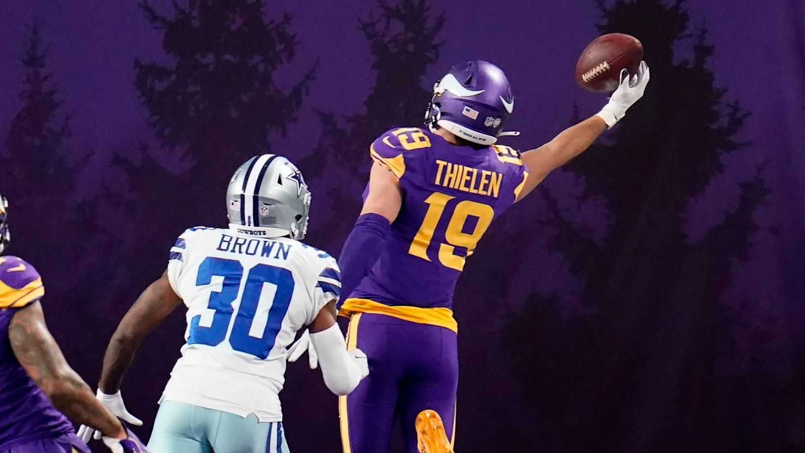 Minnesota Vikings wide receiver Adam Thielen (19) catches a 2-yard touchdown pass ahead of Dallas Cowboys cornerback Anthony Brown (30) during the second half of an NFL football game, Sunday, Nov. 22, 2020, in Minneapolis.