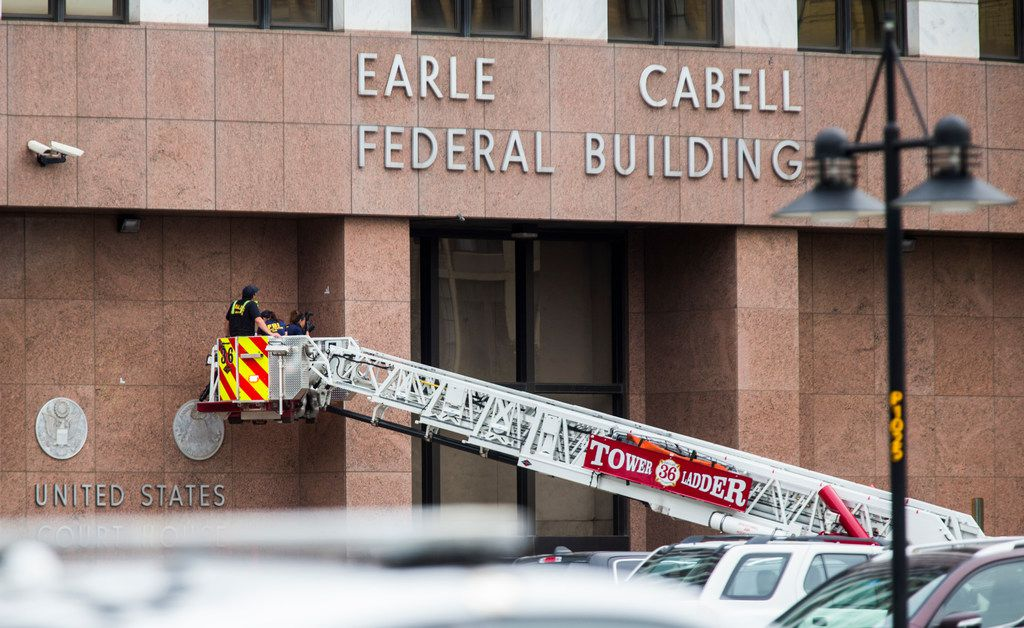 FBI and other law enforcement officials inspect the Earle Cabell Federal Building on Tuesday in Dallas.  Brian Clyde, 22, opened fire on the building. He was shot by officers and died in the parking lot. (Ashley Landis/The Dallas Morning News)