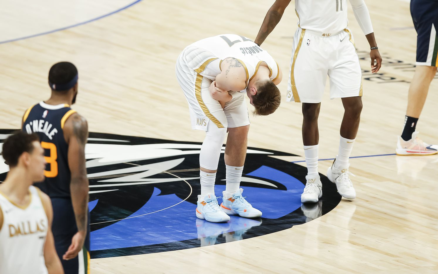 Dallas Mavericks guard Luka Doncic (77) grabs his right arm in pain during the second half of an NBA basketball game against the Utah Jazz in Dallas, Monday, April 5, 2021. Doncic would remain in the game. (Brandon Wade/Special Contributor)
