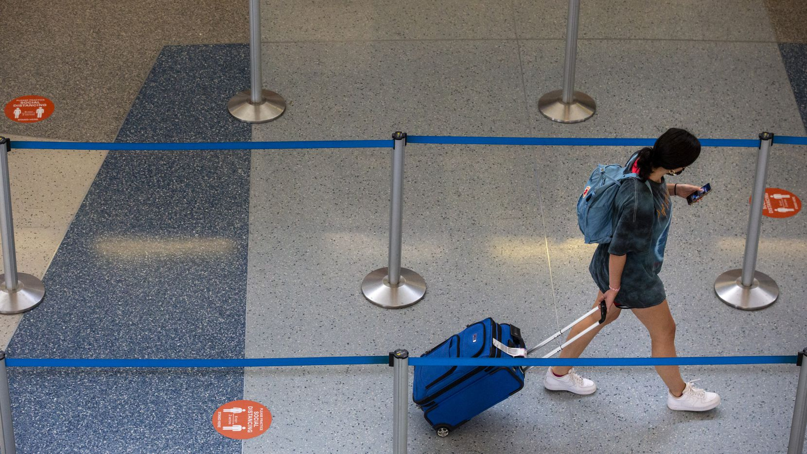 A passenger walks past social distancing markers in Terminal D at DFW International Airport.