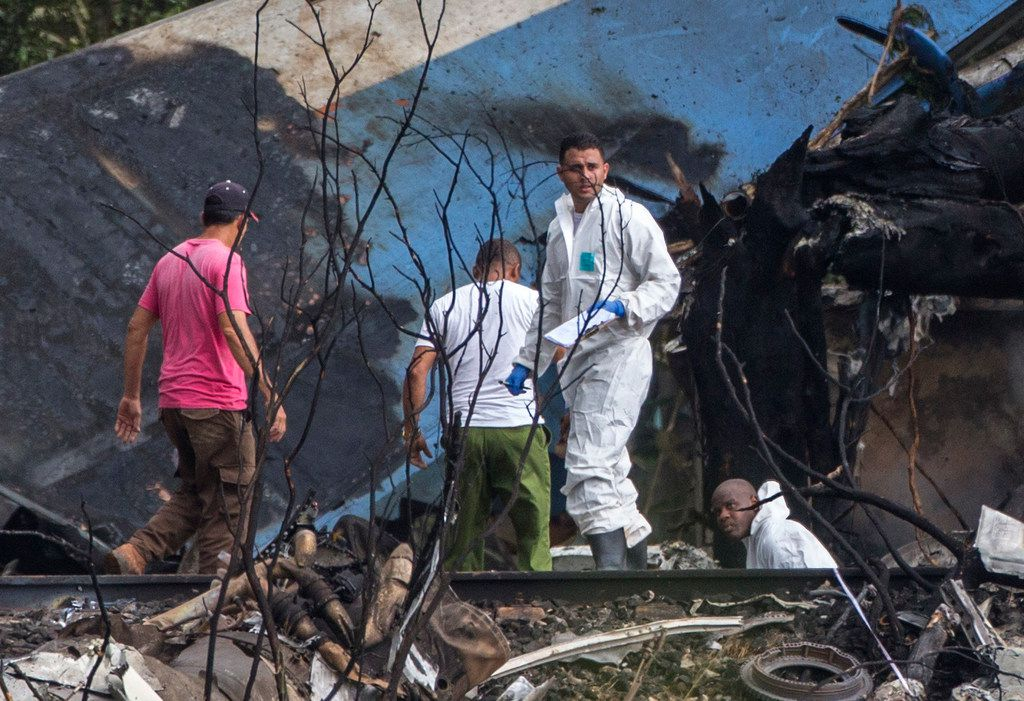 Forensic investigators and Ministry of Interior officers sift through the remains of a Boeing 737 that plummeted into a yuca field with more than 100 passengers on board, in Havana, Cuba, Friday, May 18, 2018.