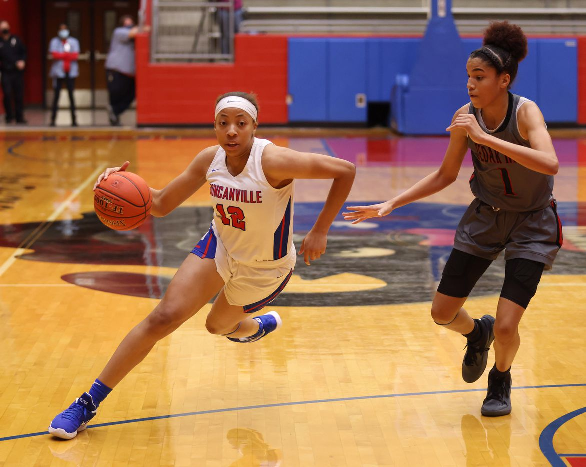 Duncanville's Zaria Rufus (12) drives towards the basket as Cedar Hill's Jadyn Atchison (1) defends  during the second half of play at Sandra Meadows Arena at Duncanville High School on Tuesday, January 12, 2021 in Dallas. Duncanville defeated Cedar Hill 63-42. (Vernon Bryant/The Dallas Morning News)