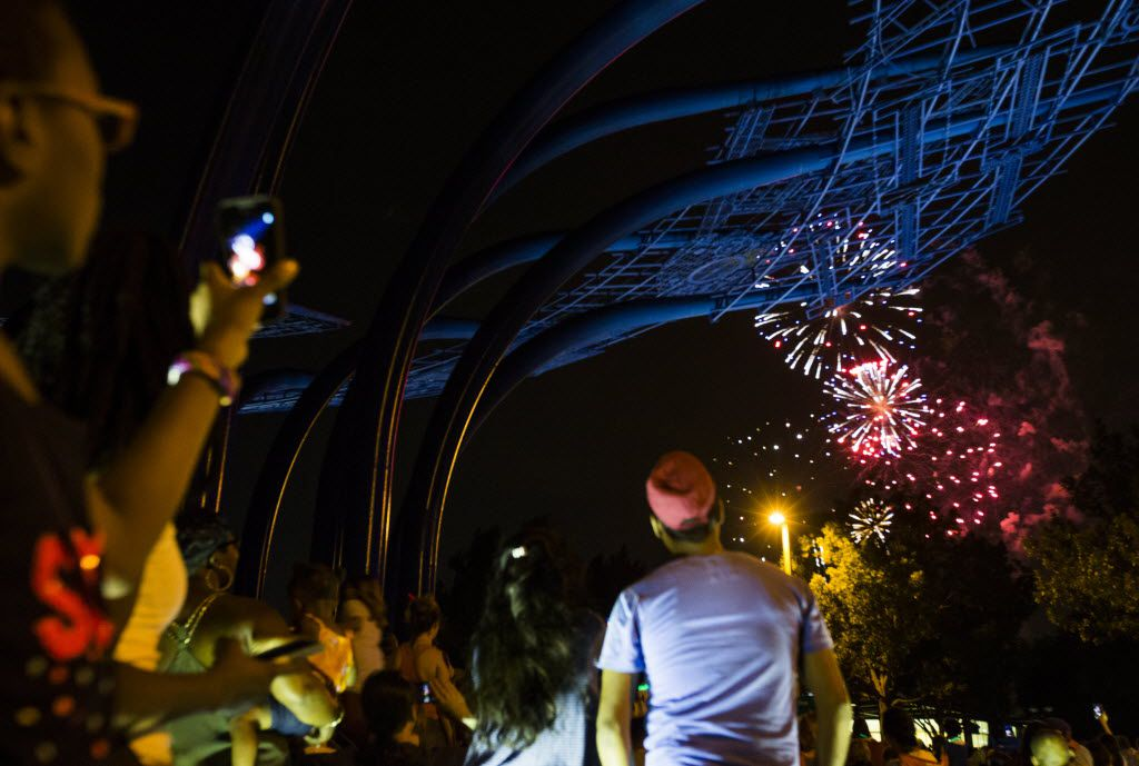 Spectators watch fireworks from the Blueprints sculpture during the Addison Kaboom Town! festival and fireworks show.