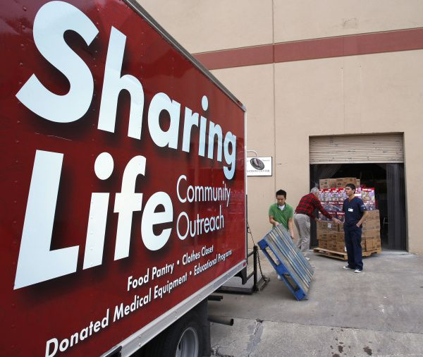 Workers unload food and diapers at Sharing Life Community Outreach.
