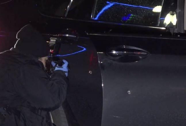 A police photographer shoots photos of a car that was hit in a drive-by shooting Friday morning in Uptown Dallas.