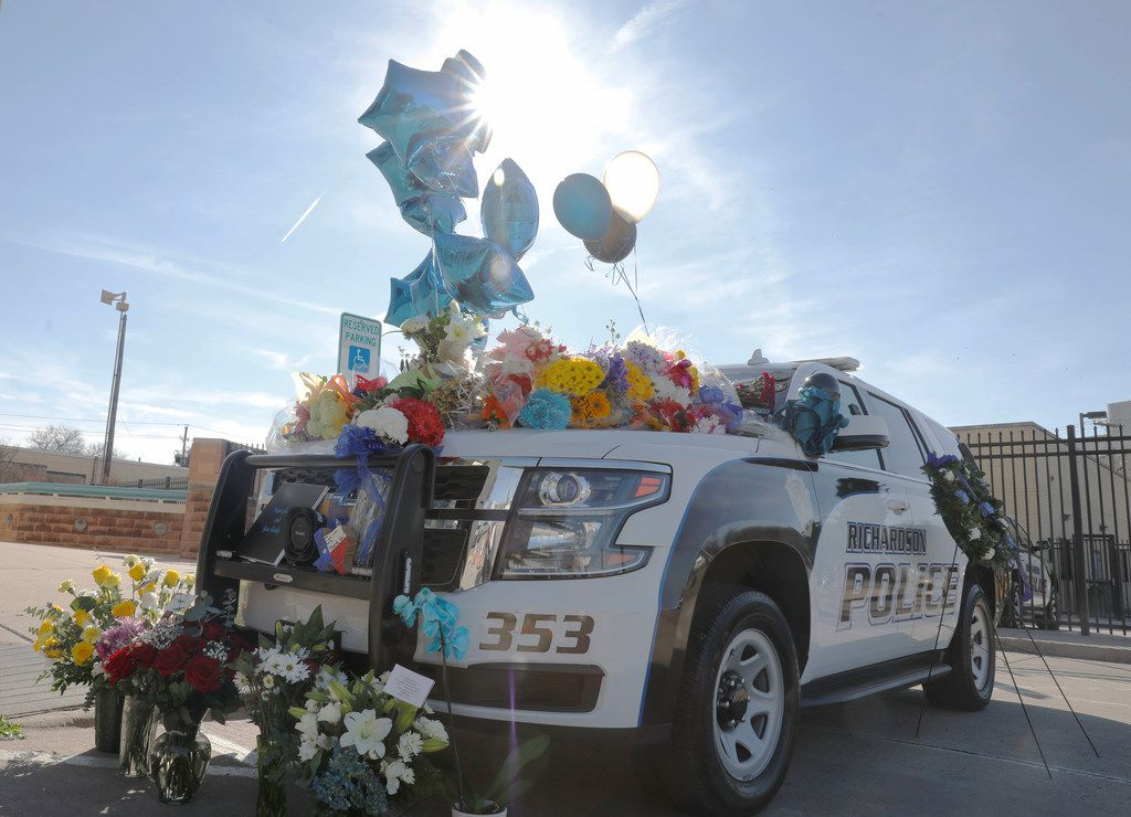 Flowers, balloons and other items were placed on a Richardson police vehicle at the Richardson police headquarters, Thursday, Feb. 8, 2018. Richardson police officer David Sherrard was fatally shot Wednesday night at an apartment complex.