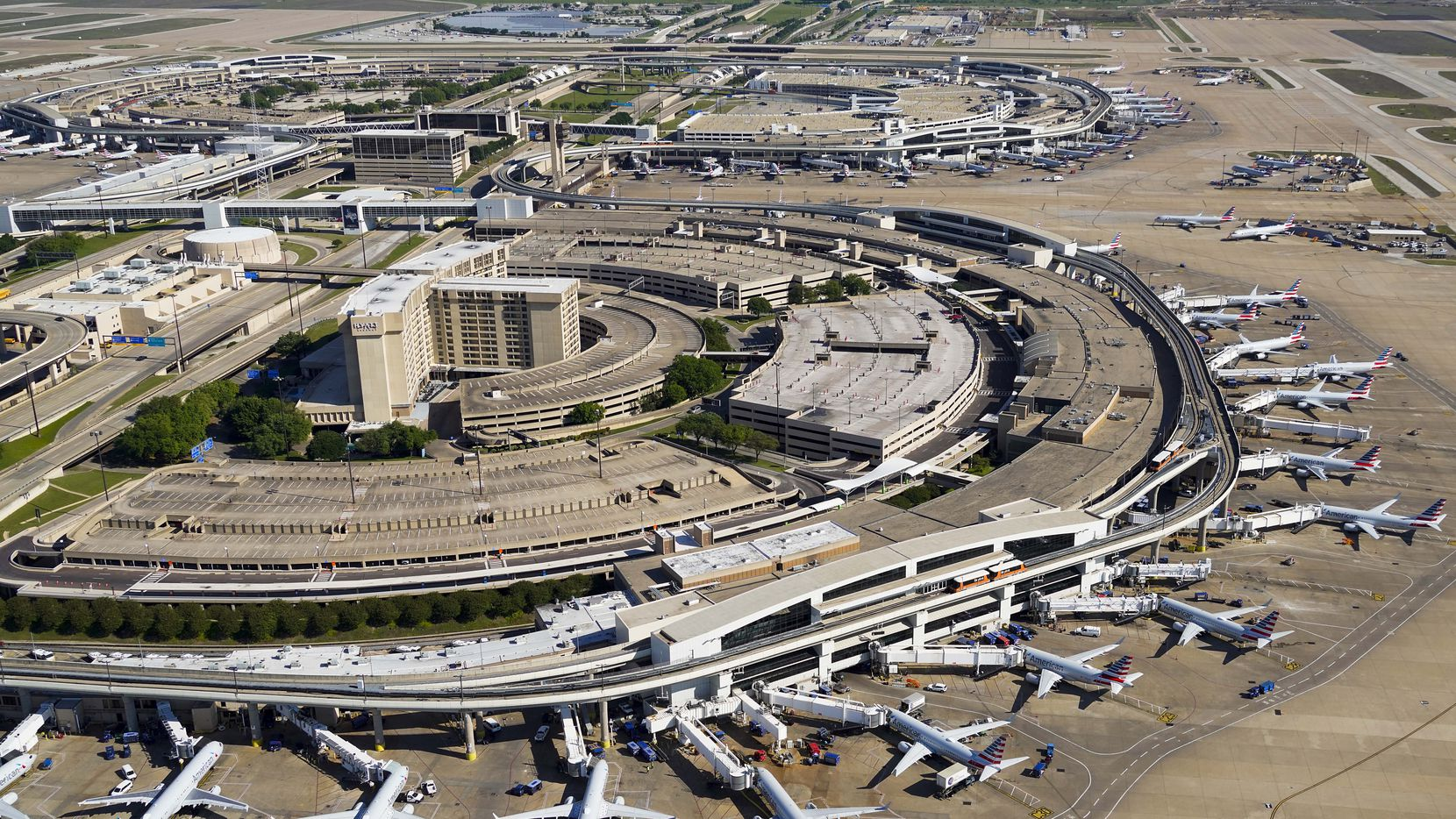 Aerial view of American Airlines aircraft at the gates of Terminal C (bottom) and Terminal A (top) at Dallas Fort Worth (DFW) International Airport on April 16, 2020.