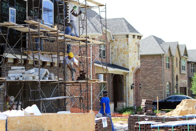 Masons work in LionsGate Homes' Creekside community off Audelia Road. LionsGate was recently bought by Ryland Homes, a California company that's one of the nation's largest homebuilders.