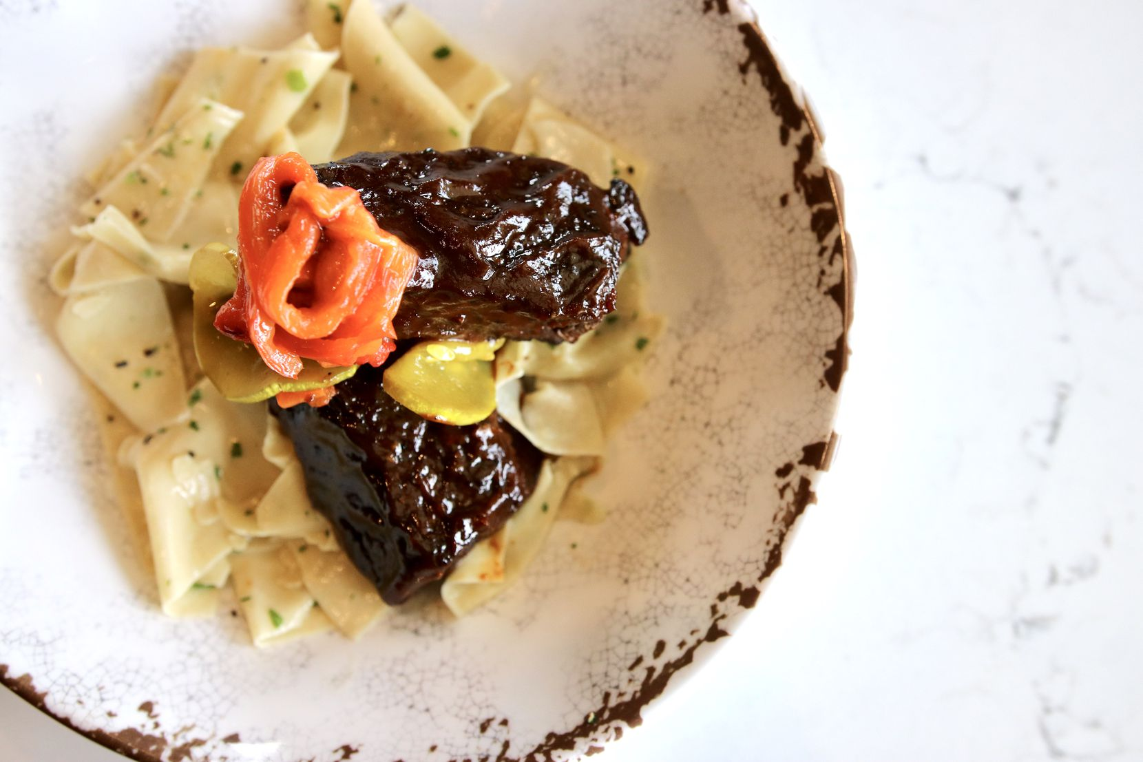 "Chef Stephan Pyles' chipotle short ribs with pappardelle noodles utilize Fireside Pies' wood-burning ovens. Pyles says they're ""a really different flavor profile than anything that's currently on the menu because of the barbecue sauce [served on the short ribs]."" The restaurants make the pastas in-house."