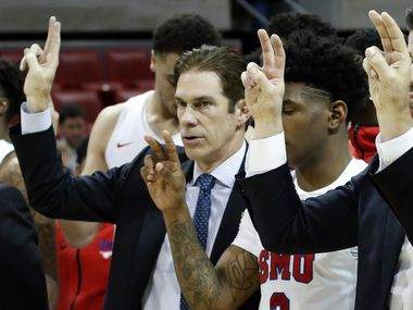 SMU head coach Tim Jankovich pauses with players and coaches for the playing of the school song following their 58-53 victory over Memphis. The two teams from the NCAA's American Athletic Conference played their men's basketball game at SMU's Moody Coliseum in Dallas on February 25, 2020.