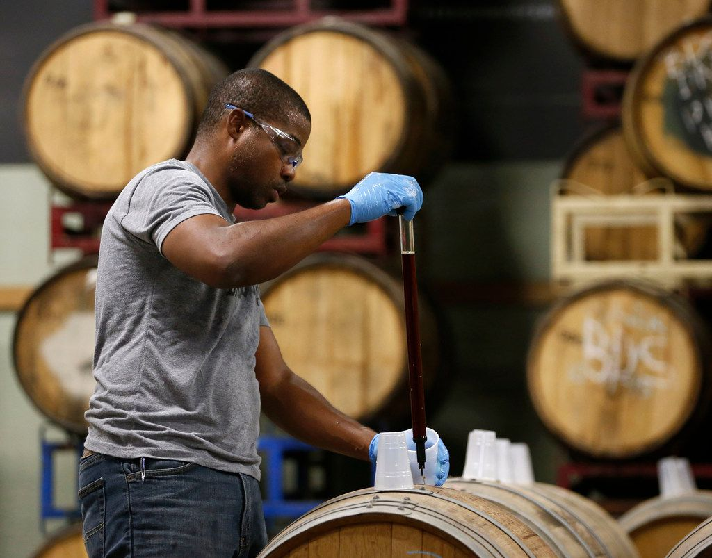 Barrett Tillman, brewer at Deep Ellum Brewing Co., works on pulling samples from barrels before opening to taste and catalog the beer for future release at Deep Ellum Brewing Co. in Dallas on Friday, September 22, 2017.