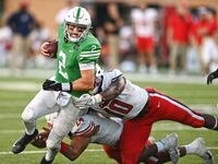 UNT quarterback Austin Aune (2) gains yardage while dragging Liberty defenders during their game at Apogee Stadium Saturday, October 23, 2021, in Denton, Texas. Photo by Al Key/DRC