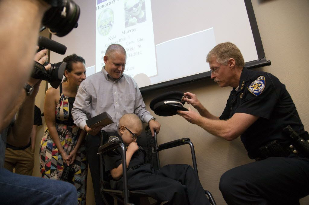 Kyle Murray, 10, gets a police hat from Frisco Police Chief John Bruce, who made the terminally ill boy an honorary police officer for the day in September 2014.  An honor guard attended Kyle's funeral the following month.