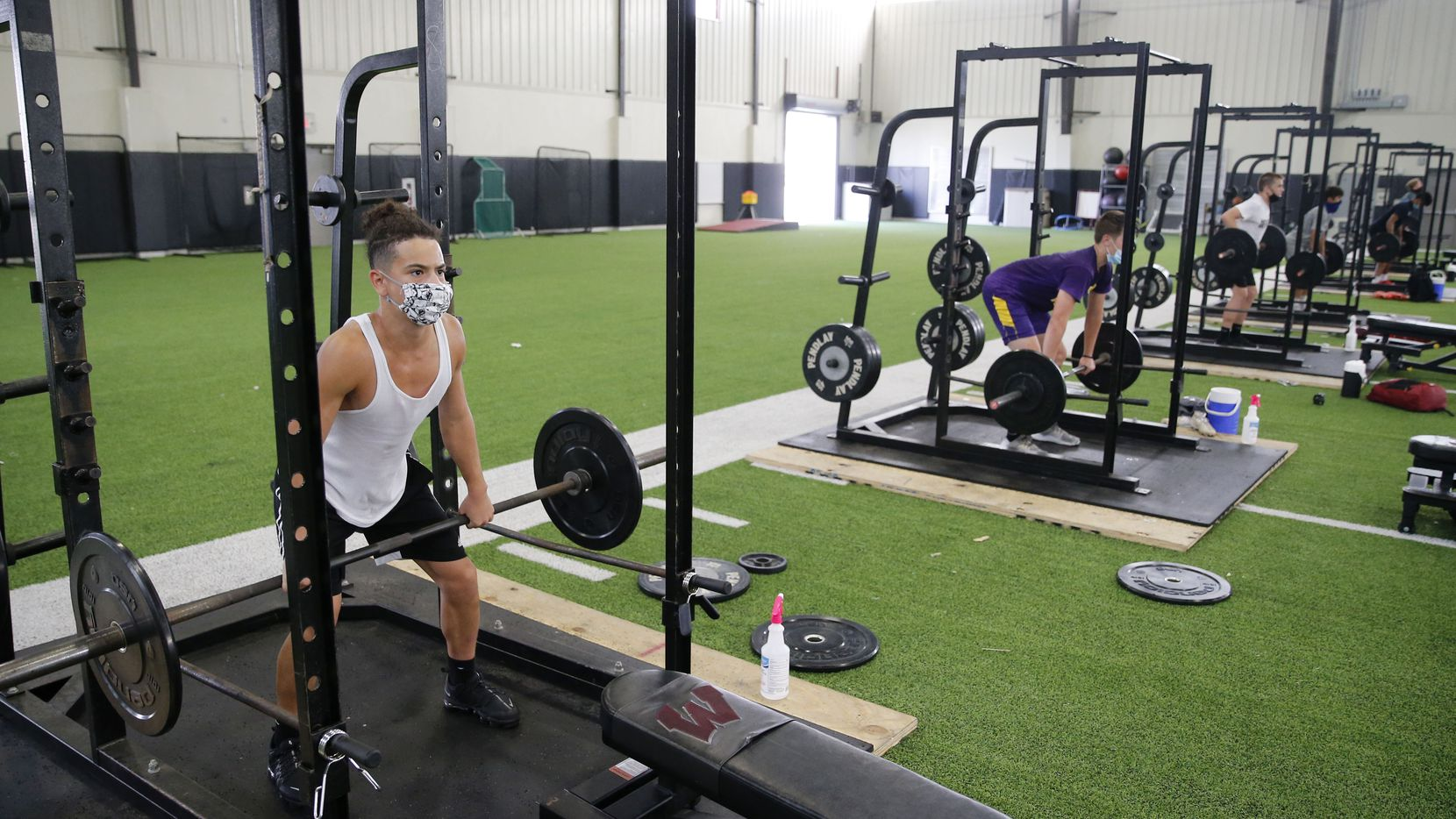 Wylie's Brandon Smith works out during football practice at Wylie High School in Wylie, Texas on Thursday, July 23, 2020. Players have their own station and sanitizer to use on the weights.